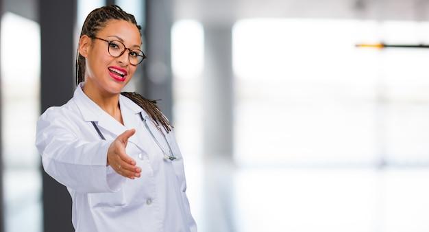 Портрет молодой женщины чернокожего доктора, протягивающей руку, чтобы поприветствовать кого-то или жестикулирующей, чтобы помочь, счастливой и взволнованной