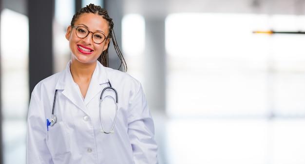Портрет молодой чернокожей женщины доктора веселый и с широкой улыбкой, уверенный в себе, дружелюбный и искренний, выражающий позитивность и успех