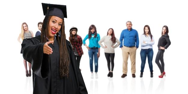 Молодой выпускник черная женщина в косах протягивая руку, чтобы приветствовать кого-то или жесты, чтобы помочь, счастливым и взволнованным