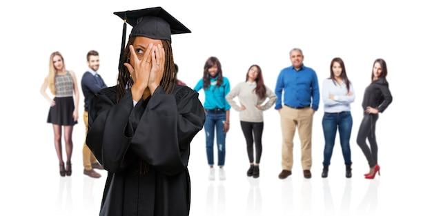 Молодой выпускник черная женщина в косах чувствует себя обеспокоенным и испуганным, смотрит и закрывает лицо, понятие страха и тревоги