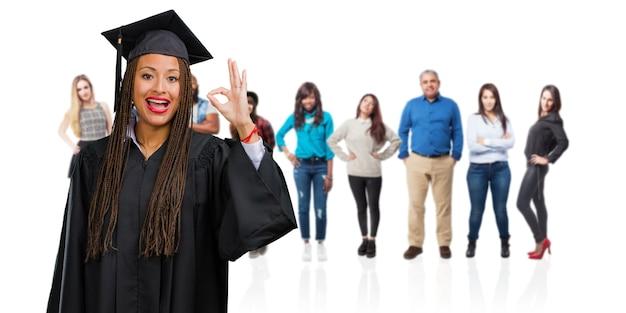 Молодой выпускник негритянка в косичках веселый и уверенный делает ок жест, взволнован и кричит, концепция одобрения и успех