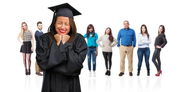 Молодой выпускник негритянки в косичках очень рад и взволнован, поднимает руки, празднует победу или успех, выигрывает в лотерею