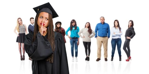 Молодые выпускники чернокожей женщины носить косы, сохраняя в тайне или прося молчания, серьезное лицо, концепция послушания