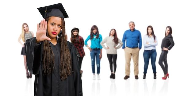 Молодой выпускник черная женщина носить косы серьезные и решительные, положить руку впереди, остановить жест, отрицать концепцию