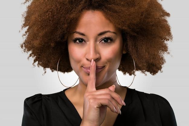 Афро женщина делает жест молчания, лицо крупным планом