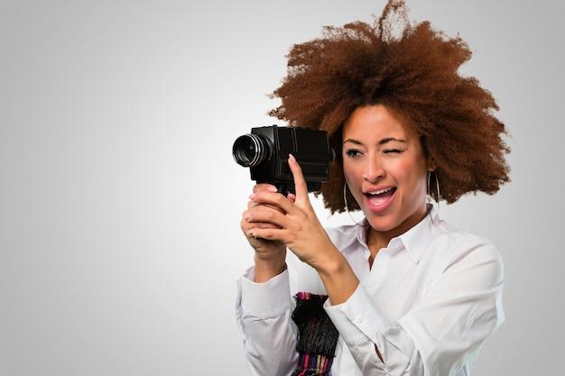 Молодая афро женщина снимается в винтажной видеокамере