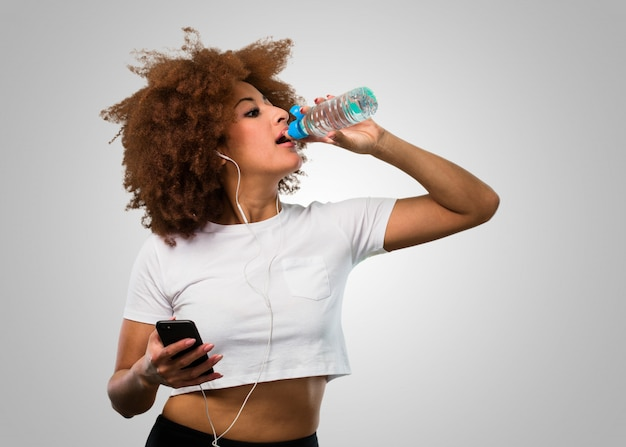 同時に携帯電話と飲料水を保持している若いフィットネスアフロ女性