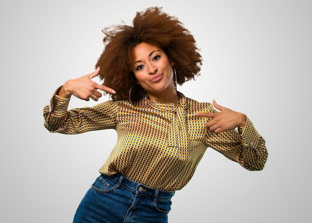 彼女のシャツを指しているアフロ女性