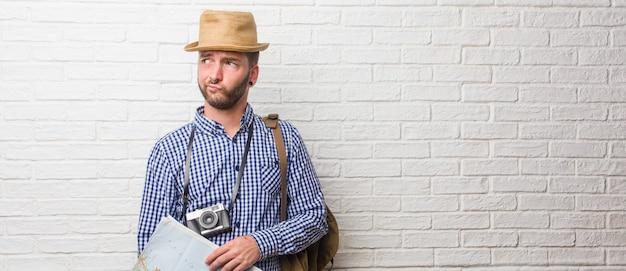 バックパックとビンテージカメラを身に着けている若い旅行者男が疑問や混乱、アイデアを考えてまたは何かを心配しています。地図を持っています。