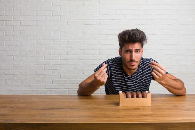 悲しい、落ち込んでいるテーブルの上に座って、必要なジェスチャーをして、慈善団体、貧困と悲惨の概念に復元する若いハンサムで自然な男。チョコレートドーナツを食べる