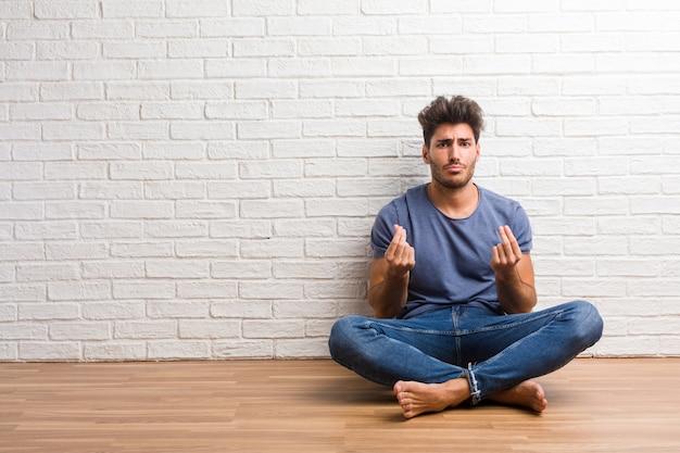 若い自然な男は悲しい、落ち込んでいる木の床の上に座る、必要性のジェスチャーを作る、慈善団体、貧困と悲惨さの概念に復元