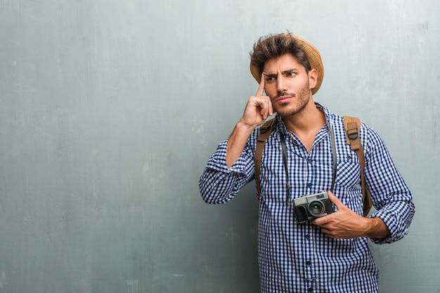 Молодой красивый путешественник, одетый в соломенную шляпу, рюкзак и фотоаппарат, думая и глядя вверх, смущенный идеей, будет пытаться найти решение