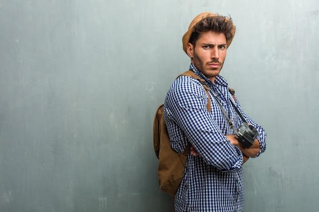 Молодой красавец-путешественник в соломенной шляпе, рюкзаке и фотоаппарате очень злой и расстроенный, очень напряженный, кричащий яростный, негативный и сумасшедший