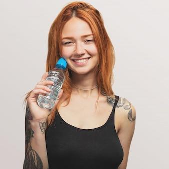 Портрет довольно рыжая девушка держит бутылку воды
