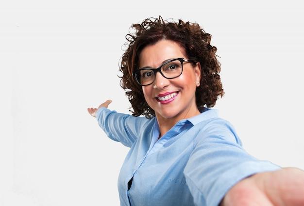 Среднего возраста женщина улыбается и счастлива, принимая селфи, держа камеру, взволнован своим отпуском или важным событием, веселое выражение