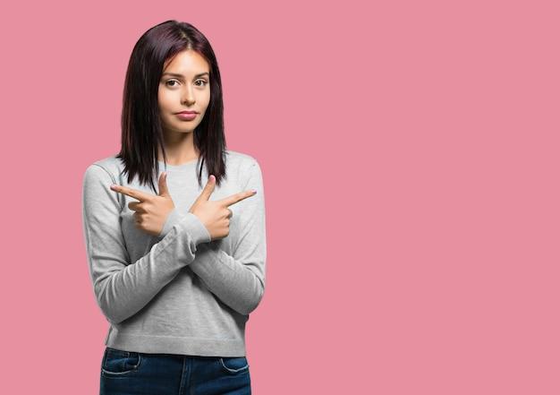 Молодая симпатичная смущенная и сомнительная женщина, решающая между двумя вариантами, концепция нерешительности