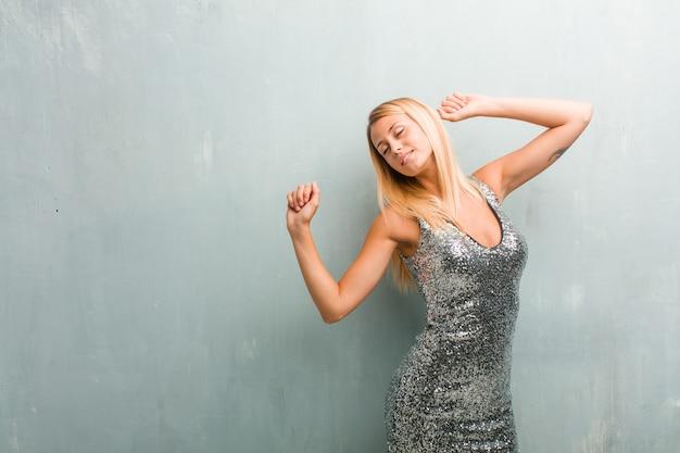 Портрет молодой элегантной белокурой женщины слушая музыку, танцуя и имея удовольствие, двигая, крича и выражая счастье, концепцию свободы