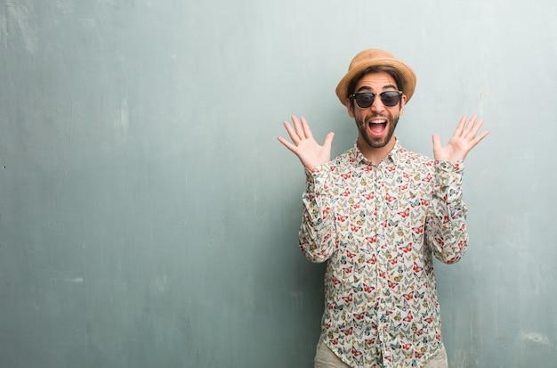 カラフルなシャツを着て幸せ叫んで若い旅行者の男