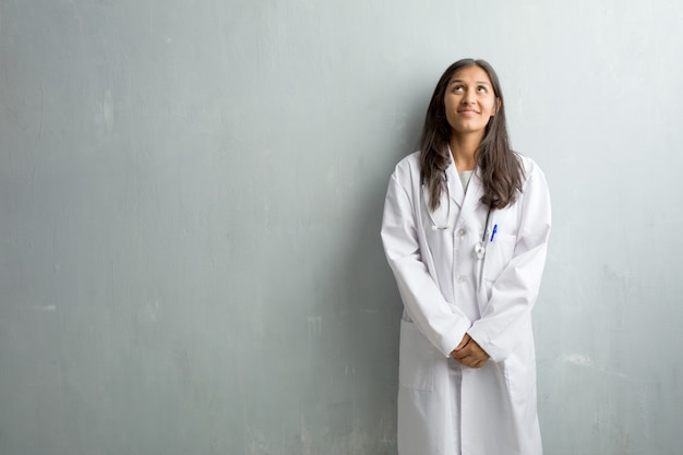 見上げる、楽しい何かを考えていると考えを持つ壁に対して若いインド人医師女性