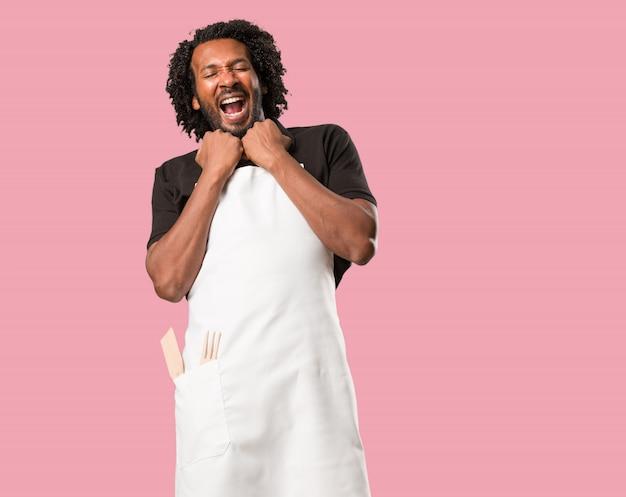 ハンサムなアフリカ系アメリカ人のパン屋は非常に幸せで、興奮して、腕を上げて、勝利または成功を祝います