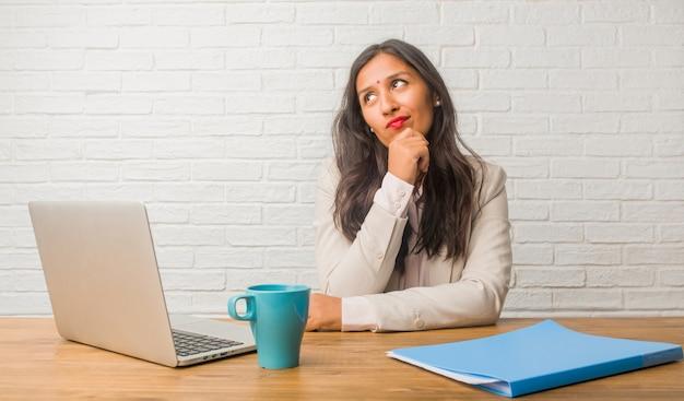 Молодая индийская женщина в офисе, думая и глядя вверх, смущенный идеей