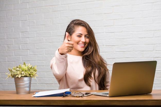 Портрет молодой женщины латинской, сидя на своем столе, веселый и возбужденный