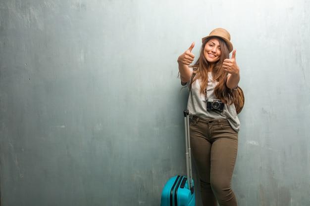 陽気で興奮して、笑みを浮かべて、彼女の親指を上げる壁に対して若い旅行者ラテン女性の肖像画