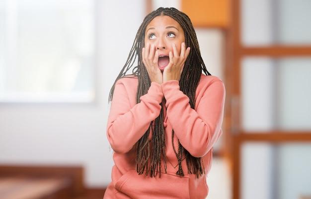 非常に怖いと恐れ、何かの絶望的なお下げを身に着けている若い黒人女性の肖像画