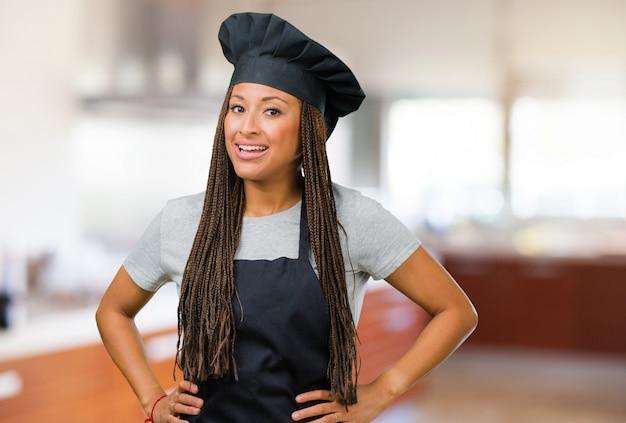 Портрет молодой женщины черный пекарь с руки на бедрах