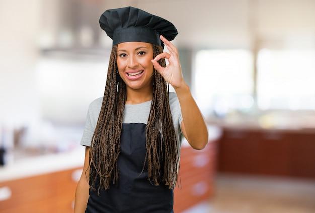 Портрет молодой женщины черный пекарь веселый и уверенно делает хорошо жест