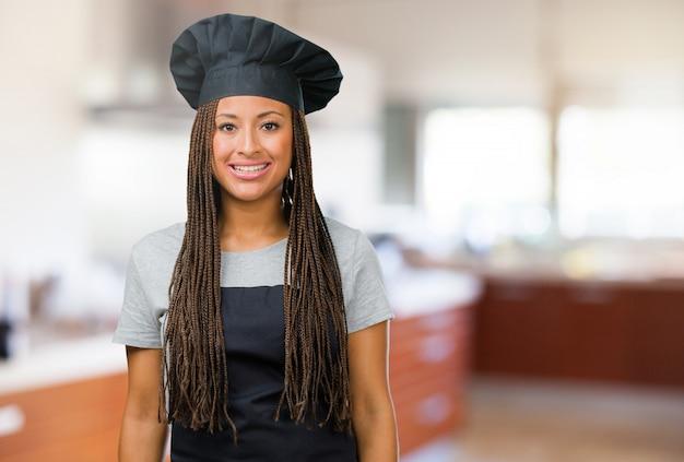 Портрет молодой женщины черного пекаря веселый и с широкой улыбкой, уверенный в себе, дружелюбный и искренний