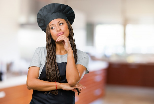 Портрет молодой женщины черный пекарь, думая и глядя вверх, смущенный идеей