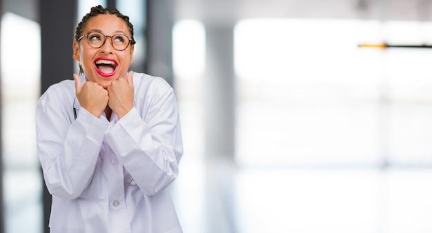 Портрет молодой женщины чернокожего доктора очень счастлив и взволнован