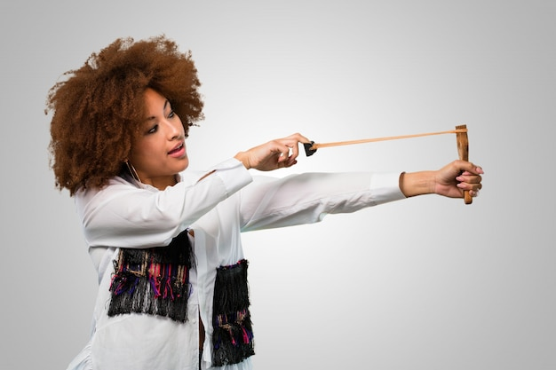 Молодая афро женщина, держащая рогатку