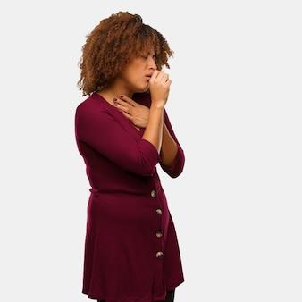 Молодая черная афро женщина кашляет, болеет из-за вируса или инфекции
