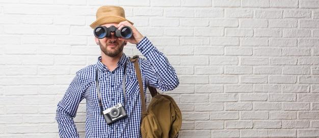 バックパックと腰に手でビンテージカメラを身に着けている若い旅行者男