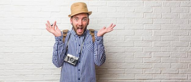 バックパックと幸せを叫んでビンテージカメラを身に着けている若い旅行者男