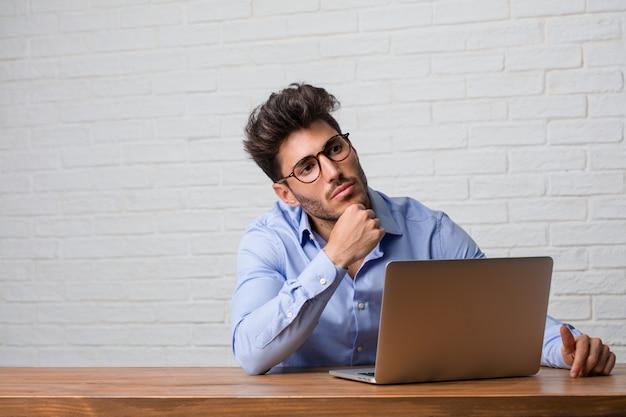 座っていると考えて見上げるラップトップに取り組んでいる若手実業家