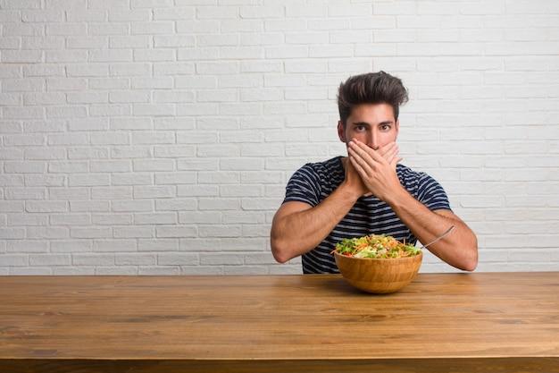 口を覆っているテーブルの上に座っている若いハンサムで自然な男