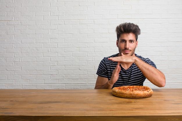 疲れて退屈、タイムアウトジェスチャーを作るテーブルの上に座っている若いハンサムで自然な男