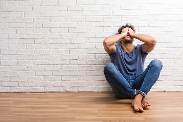 若い自然な男はイライラして絶望的な怒っていると頭の上の手で悲しい木の床の上に座る