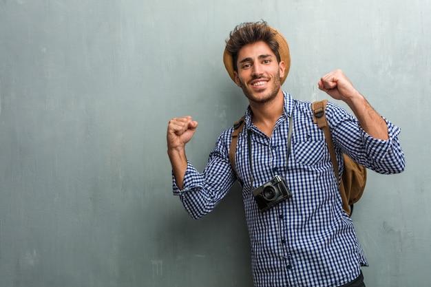 Молодой красавец путешественник в соломенной шляпе, рюкзаке и фотоаппарате очень счастлив