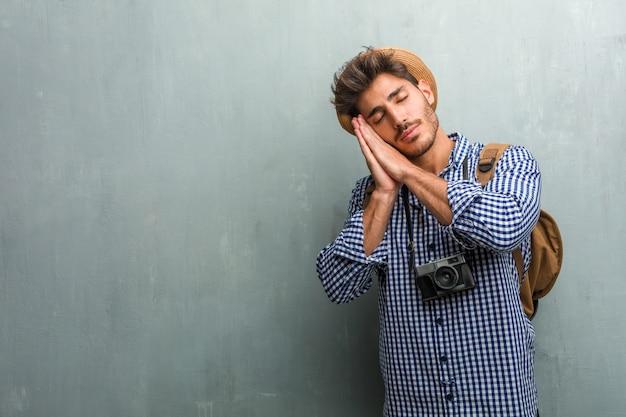Молодой красивый путешественник мужчина в соломенной шляпе, рюкзаке и фотоаппарате устал и очень сонный