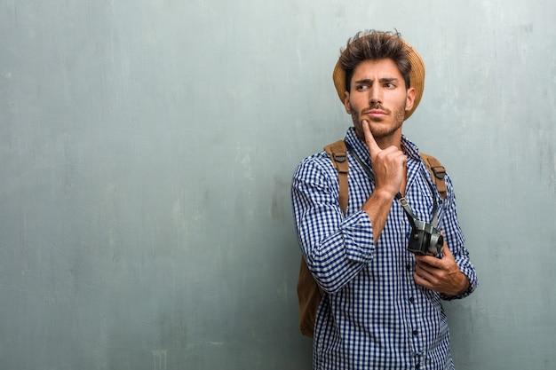 Молодой красивый путешественник человек в соломенной шляпе, рюкзак и фотоаппарат, думая и глядя вверх