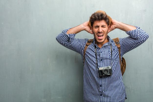 Молодой красивый путешественник человек в соломенной шляпе, рюкзак и фотоаппарат сумасшедший и отчаянный