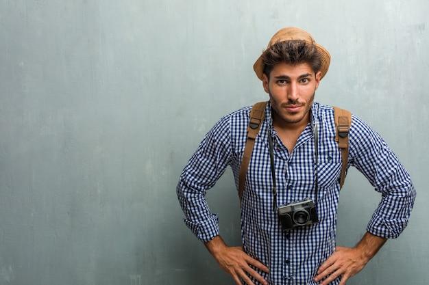 Молодой красавец путешественник в соломенной шляпе, рюкзаке и фотоаппарате очень зол и расстроен