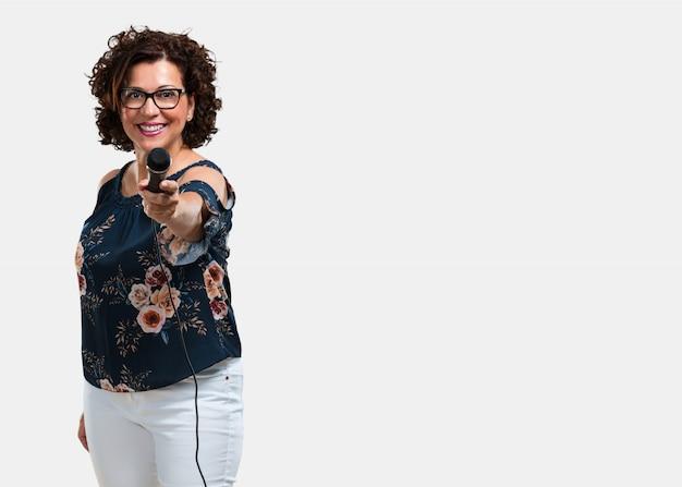 Среднего возраста женщина счастлива и мотивирована, поет песню с микрофоном