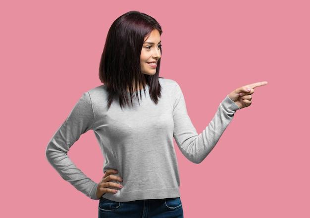 側に指している若いきれいな女性、笑みを浮かべて驚いた、自然でカジュアルな何かを提示