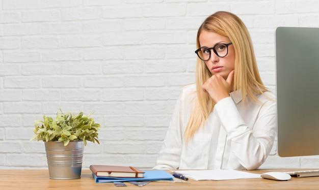 彼女の机の上に座って考えて見上げるタスクをやっている若い学生の肖像画