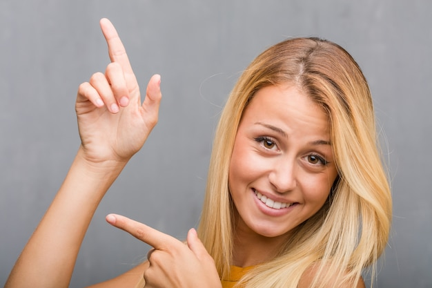 顔のクローズアップ、側を指している自然な若いブロンドの女性の肖像画、